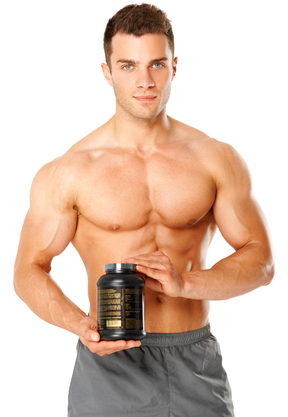 Muscular man holding container of training supplements